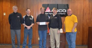 Courtesy Photo McPherson County Food Bank President Gary Casebeer (center) accepts a donation from AGCO employees in Hesston in the amount of $8,100.