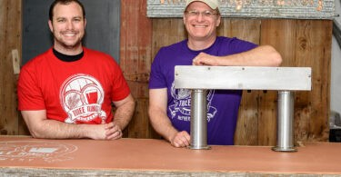 Photos by Jeff Heidel Three Rings owners Ian Smith and his father Michael Smith at the sampling bar and by the brewing equipment of their new brewery. The brewery opens Friday and will sell alcohol for consumption off premises.