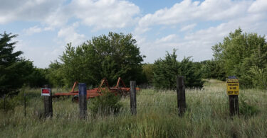 The end of the trail near Pawnee and 13th Ave. Signs, barbed wire fence and farm equipment block access to the former railroad bed that crosses property owned by Clinton and Kimbra Sides to the north. The Central Kansas Conservancy rail group filed a lawsuit to gain access to the easement.
