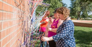 Students in the Sculpture II class at McPherson College work on the yarn bomb installation. Pictured from left are: Chelsie Whittier, Shelby Augustine, Morgan Strnad, and Lisa Koehn.