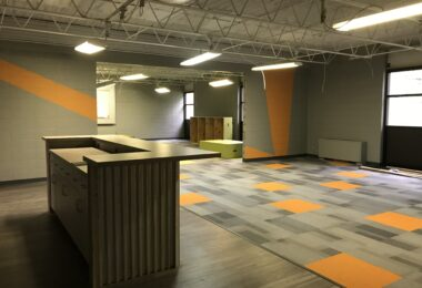 """The new youth center at the First United Methodist Church is highlighted with pops of color in an overall """"industrial feel."""" The youth center has a kitchen area and raised platforms that can be moved and used for different purposes."""