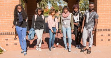Some of the Congolese students attending McPherson College meet in the gazebo on their way to class.